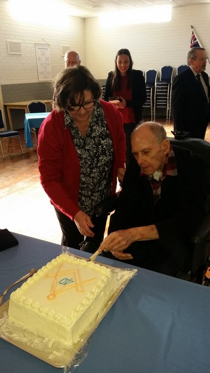 Alf cutting his cake with his daughter in attendance